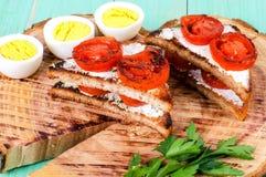 Smörgåsar med stekte tomater och kokade högg av ägg Royaltyfri Fotografi
