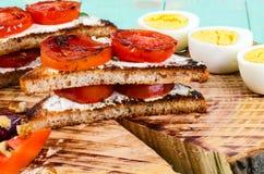 Smörgåsar med stekte tomater och kokade högg av ägg Royaltyfri Foto