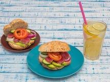 Smörgåsar med tonfisk och grönsaker i plattor, ett exponeringsglas av lemonad på en tabell royaltyfria bilder