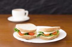 Smörgåsar på en platta och en kopp kaffe på en träbakgrund Fotografering för Bildbyråer