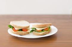 Smörgåsar på en platta på en träbakgrund arkivfoton