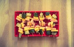 Smörgåsar på pinnar på en röd platta Arkivfoto
