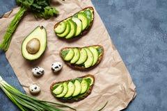 Smörgåsar rostar med avokadot, guacamole och spenat på pergament på en konkret bakgrund Sund frukost eller lunch Royaltyfria Foton