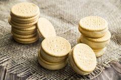 Smörgåsar som göras från kakor och glass med förtätat, mjölkar på en tabell med säckväv Fotografering för Bildbyråer