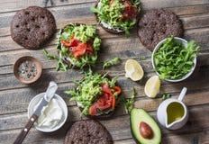 Smörgåsen för rågbröd med gräddost, den rökte laxen, arugula, mosade avokadot på lantlig träbakgrund, bästa sikt Sund delici Royaltyfria Foton