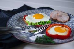 Smörgåsen med ägget, skinka, ost, rostat bröd och sallad lämnar lögner på en platta med tomaten och dill arkivfoto