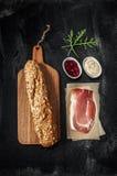 Smörgåsrecept för Prosciutto (parma skinka) - ingredienser på svart arkivfoton