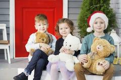 Sm? barn i f?rv?ntan av det nya ?ret och jul Tre lilla ungar har gyckel och spelar med nallebj?rnar arkivfoton
