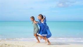 Sm? flickor har gyckel med strandhandduken under tropisk semester stock video