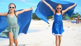 Sm? flickor har gyckel med strandhandduken under tropisk semester arkivfilmer