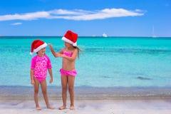Små flickor i jultomtenhattar under sommarsemester Arkivfoton
