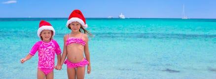 Små flickor i jultomtenhattar under sommarsemester Royaltyfri Fotografi
