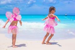 Små flickor med fjärilsvingar har den roliga stranden Arkivbild