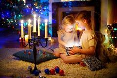 Små flickor som öppnar en magisk julgåva Arkivfoton