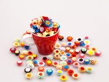Små färgrika pappers- blommor i en kopp kaffe Arkivfoto