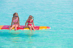 Små förtjusande flickor på en surfingbräda i Royaltyfri Fotografi
