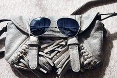 Små gråa kvinnors handväska och solglasögon Royaltyfri Foto