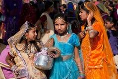 Små indiska damer har gyckel i folkmassan av folk Arkivfoto