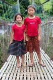 Små nepalesiska flickor på den hunging upphängningbron för rep Arkivfoto