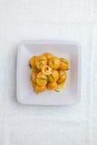 Små nya kokta potatisar kastade med nya örter i olivoljanolla Arkivbild