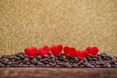 Små röda satänghjärtor med bokstäver på kaffebönor med guld- fira för bakgrund, för valentindag eller för bröllopdag Arkivbilder