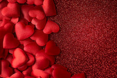 Små röda satänghjärtor på rött blänker textur-, valentin- eller moderdagbakgrund Royaltyfri Fotografi