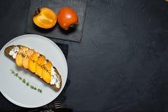 Sm?rg?s med persimonet och mjuk ost p? en svart bakgrund med utrymme f?r text royaltyfria bilder