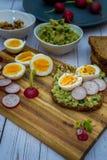 Sm?rg?sar med den nya r?disan f?r avokadoguacamole och det kokta ?gget arkivfoto