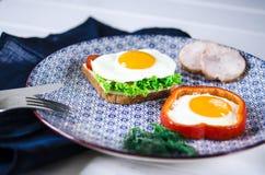 Sm?rg?sen med ?gget, skinka, ost, rostat br?d och sallad l?mnar l?gner p? en platta med tomaten och dill arkivbilder