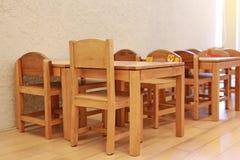 Sm? skrivbord och stolar f?r unge i studentklassrum arkivfoton