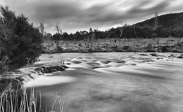 SM Thredbo Riv Riffle BW. Black white of dark blurred Thredbo river going over rocky riffles at sunset between hills and mountains in Kosciuszko national park Stock Images