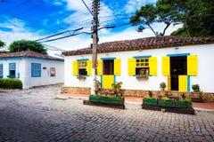 Små vithus med det gula fönstret stänger med fönsterluckor i Buzios, Braz Arkivbild