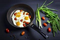 Smażący jajka z pomidorami w świeżych cebulach na ciemnym tle i niecce Odgórny widok zdjęcia stock