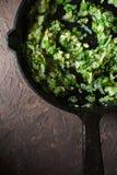 Smażąca cebula z zieleniami w kulinarnym niecki vertical Fotografia Stock