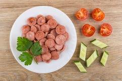 Smażąca kiełbasa, pietruszka w talerzu, kawałki pomidor i ogórek, zdjęcia royalty free
