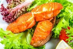Smażący łosoś, sałaty Lollo rossa, cytryna kliny, czereśniowy pomidor, Obrazy Royalty Free