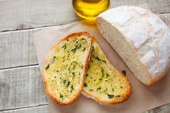 Smażący chleb z oliwa z oliwek, czosnkiem i ziele na drewnianym stole, Wieśniaka styl Obraz Royalty Free