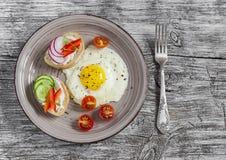 Smażący jajka, pomidory i kanapki z, ogórkiem, rzodkwią i miękkim serem, Na lekkim drewnianym stole Wieśniaka styl zdjęcia stock