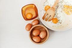 Smażący jajka w smaży niecce, śniadaniowi składniki, kuchenni akcesoria Świezi Brown jajka w Drewnianym talerzu Biały tło Odgórny Zdjęcie Royalty Free