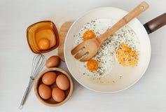 Smażący jajka w smaży niecce, śniadaniowi składniki, kuchenni akcesoria Świezi Brown jajka w Drewnianym talerzu Kulinarny ranku j Fotografia Stock