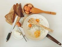 Smażący jajka w Smaży niecce, Śniadaniowi składniki Pomarańcze, chleb, masło, Porrige, fasole Coffe akcesoriów tła odosobniony ku Zdjęcia Stock