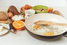 Smażący jajka w Smaży niecce, Śniadaniowi składniki Pomarańcze, chleb, masło, Porrige, fasole Coffe akcesoriów tła odosobniony ku Fotografia Royalty Free