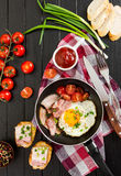 Smażący jajka z baleronem i pomidorami w niecce obraz royalty free