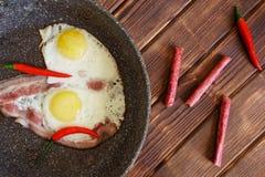 Sma??cy jajka z bekonem, uw?dzonymi kie?basami i czerwonego chili pieprzami na rocznika granitu niecce, Naturalny t?o sosnowe des obraz stock