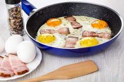 Smażący jajka z brisket w smażyć nieckę, słój z condiment, jajka, brisket w talerzu, szpachelka na drewnianym stole obrazy royalty free