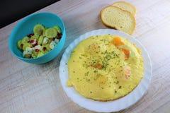 Smażący jajka z rozciekłym serem na białym talerzu z jarzynową sałatką na stronie w błękitnym naczyniu z dwa kawałkami chleb obraz royalty free