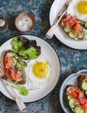 Smażący jajko, łososiowa kremowego sera kanapka i - wyśmienicie, na drewnianym tle, odgórny widok Zdjęcia Stock
