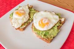 Smażący jajko na avacado guacamole i brąz grzance Obrazy Stock