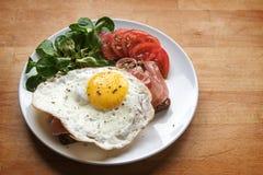 Smażący jajko na chlebie z baleronem garnirującym z zieloną sałatką i tomat zdjęcia royalty free