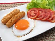 Smażący jajko z gotowanymi kiełbasami Obrazy Royalty Free
